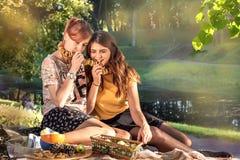 美丽的女孩食用从杯子,野餐的茶户外 图库摄影