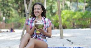 美丽的女孩饮料椰子鸡尾酒坐在棕榈树的海滩,愉快的微笑的少妇游人 股票视频