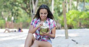 美丽的女孩饮料椰子鸡尾酒坐在棕榈树的海滩,愉快的微笑的少妇游人 影视素材