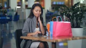 美丽的女孩饮用水和使用智能手机在购物在购物中心以后 图库摄影
