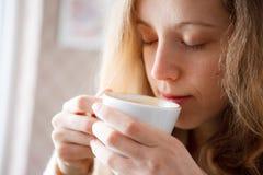 美丽的女孩饮用的咖啡。 杯热的饮料 免版税库存照片