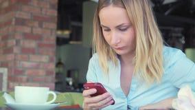 美丽的女孩饮用的咖啡和使用电话在咖啡馆 影视素材