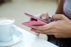 美丽的女孩饮用的咖啡和发短信与手机 免版税库存图片