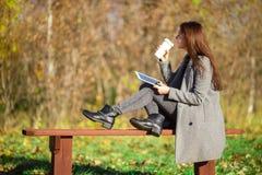 美丽的女孩饮用的咖啡在秋天公园户外 库存照片