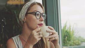 美丽的女孩饮用的咖啡,作梦和微笑在咖啡馆 图库摄影