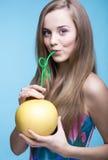 美丽的女孩饮用的柚汁通过秸杆 免版税图库摄影