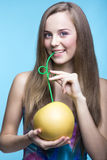 美丽的女孩饮用的柚汁通过秸杆 免版税库存图片