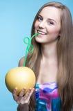 美丽的女孩饮用的柚汁通过秸杆 库存图片