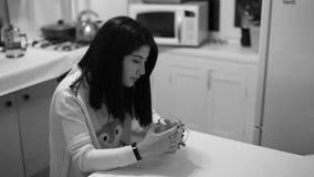 美丽的女孩饮用的茶在厨房里 股票录像