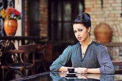 美丽的女孩饮用的茶或咖啡在咖啡馆 库存照片
