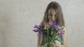 美丽的女孩高兴花捐赠的花束并且打旋 影视素材
