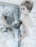 美丽的女孩,在雪的图象的白色礼服 免版税图库摄影