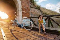美丽的女孩,坐木桥和读 免版税库存照片