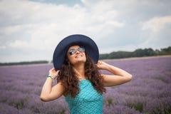 美丽的女孩,微笑在淡紫色领域 免版税图库摄影