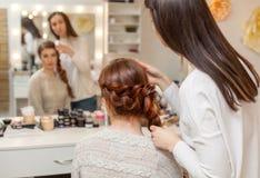 美丽的女孩,有长期的,红发长毛 美发师编织法国辫子,在美容院的特写镜头 图库摄影