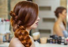 美丽的女孩,有长期的,红发长毛 美发师编织法国辫子 免版税图库摄影