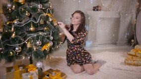 美丽的女孩,装饰圣诞树的少妇,在圣诞树上把新年玩具和球放 股票录像