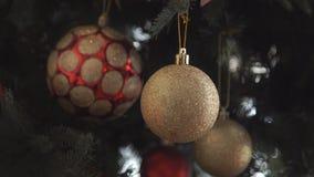 美丽的女孩,装饰圣诞树的少妇,在圣诞树上把新年玩具和球放 影视素材
