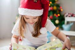 美丽的女孩,读在圣诞树前面的一本书, detai 免版税库存照片