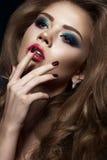 美丽的女孩以与卷毛、红色嘴唇和蓝色构成的好莱坞方式 秀丽表面和头发 库存图片