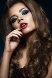 美丽的女孩以与卷毛、红色嘴唇和蓝色构成的好莱坞方式 秀丽表面和头发 免版税库存照片