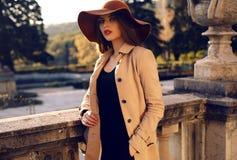 美丽的女孩以典雅的时尚在秋天公园给摆在穿衣 库存照片