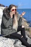 美丽的女孩 愉快的妇女走和谈话在海滩的电话与海在背景中 库存图片