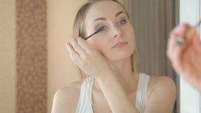 美丽的女孩绘睫毛 做构成接近的妇女 股票录像