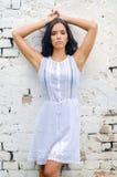 美丽的女孩画象倾斜在墙壁的白色礼服的 免版税库存图片