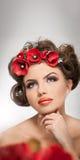 美丽的女孩画象在有红色花的演播室在她的头发和赤裸肩膀 有专业构成的性感的少妇 免版税库存照片