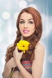 美丽的女孩画象在有黄色菊花的演播室在她的手上 有蓝眼睛的性感的少妇与明亮的花 免版税库存图片