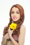 美丽的女孩画象在有黄色菊花的演播室在她的手上 有蓝眼睛的性感的少妇与明亮的花 免版税库存照片
