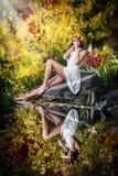 美丽的女孩画象在森林里。有神仙的神色的女孩在秋季射击。有秋季的女孩组成和发型 免版税库存图片