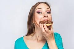 美丽的女孩画象有巧克力油炸圈饼的 免版税库存照片