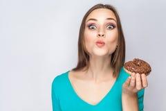 美丽的女孩画象有巧克力油炸圈饼的 免版税库存图片