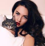 美丽的女孩画象有摆在与猫的黑发的 免版税库存照片