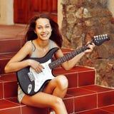 美丽的女孩画象有电吉他的 图库摄影