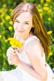 美丽的女孩画象有黄色蒲公英花束的室外在夏天,在眼睛的焦点 免版税库存图片