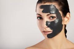 美丽的女孩画象有黑面具黏土的 免版税图库摄影