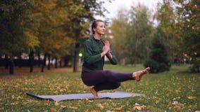美丽的女孩yogini在席子实践的平衡状况的公园行使在一腿和放松 健康 影视素材