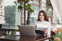 美丽的女实业家与纸一起使用户外 免版税图库摄影