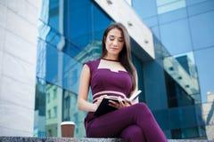 美丽的女实业家与纸一起使用户外 免版税库存图片