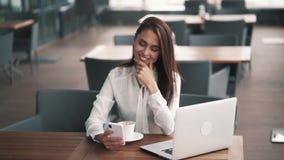 美丽的女实业家为工作在咖啡馆,慢动作使用智能手机和膝上型计算机 股票视频