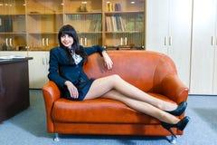 年轻美丽的女实业家休息的说谎在一个沙发在办公室 免版税库存照片