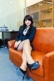 年轻美丽的女实业家休息的说谎在一个沙发在办公室 免版税库存图片