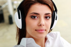 年轻美丽的女实业家听的音乐的特写镜头画象 库存照片