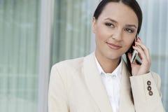 美丽的女实业家回答的手机户外 免版税库存图片