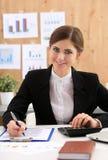 美丽的女实业家在事务的工作场所坐与pap 免版税图库摄影