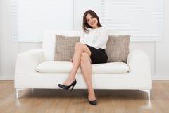 美丽的女实业家在家坐沙发 免版税图库摄影