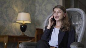 美丽的女实业家坐在扶手椅子和谈话在手机 股票视频